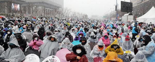 지난 2월 서울 광화문광장에서 열린 '대한민국 바로 세우기' 집회 참가자들이 눈보라 속에서 우비와 마스크 차림으로 광장 일대를 가득 메우고 있다. /연합뉴스