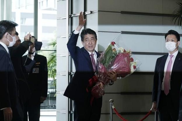 아베 신조 전 일본 총리가 16일 꽃다발을 안고 도쿄 총리관저를 떠나면서 손을 흔들고 있다. /연합뉴스