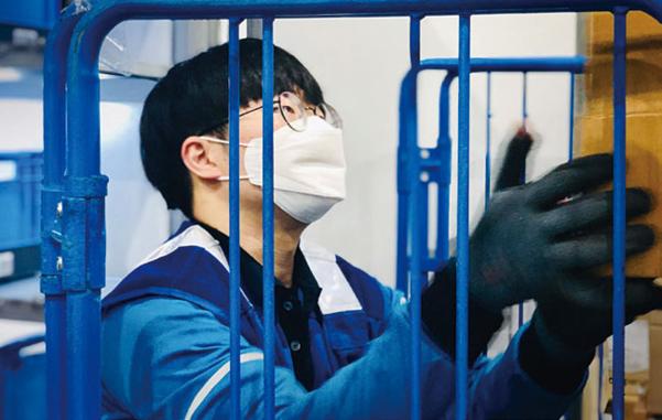 쿠팡 물류센터에서 한 직원이 마스크를 쓰고 일하고 있다. / 쿠팡