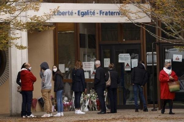 17일 프랑스 파리 외곽 콘플란스 사인테호노린에서 교사가 살해된 뒤 아이들과 학부모들이 존경의 마음을 담아 보이스다울네 중학교 앞에 꽃을 놓고 있다. /EPA 연합뉴스