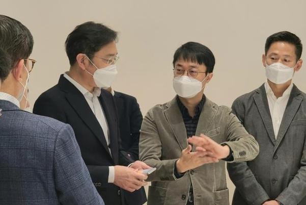 이재용 삼성전자 부회장이 12일 서울 우면동 R&D캠퍼스에서 연구진들과 만난 자리에서 한 모바일기기를 손에 들고있다. 업계에서는 익스펜더블폰이라는 관측이 나온다. /삼성전자