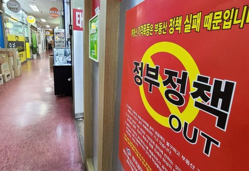 지난 19일 서울 시내 한 부동산 중개업소 외벽에 기존 정부정책을 규탄하는 홍보물이 부착되어 있다. /연합뉴스