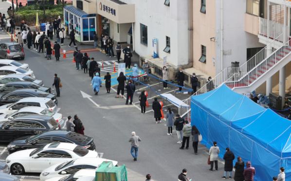 25일 동작구청 주차장에 설치된 선별진료소 앞에서 시민들이 길게 줄을 서서 코로나 검사를 기다리고 있다. /연합뉴스