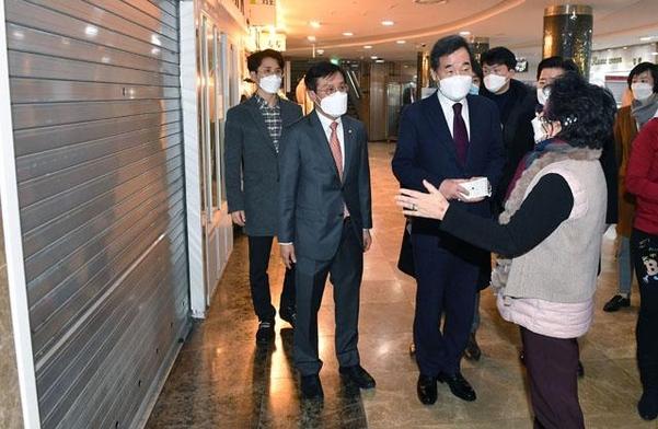 이낙연 대표가 14일 서울 영등포 지하상가 내 문을 닫은 상가 앞에서 상인들의 고충을 듣고 있다. /연합뉴스