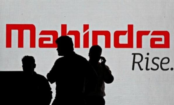 마힌드라 직원들이 마힌드라 회사 로고 앞에 서서 투자설명회를 준비하고 있다. /뭄바이로이터연합뉴스
